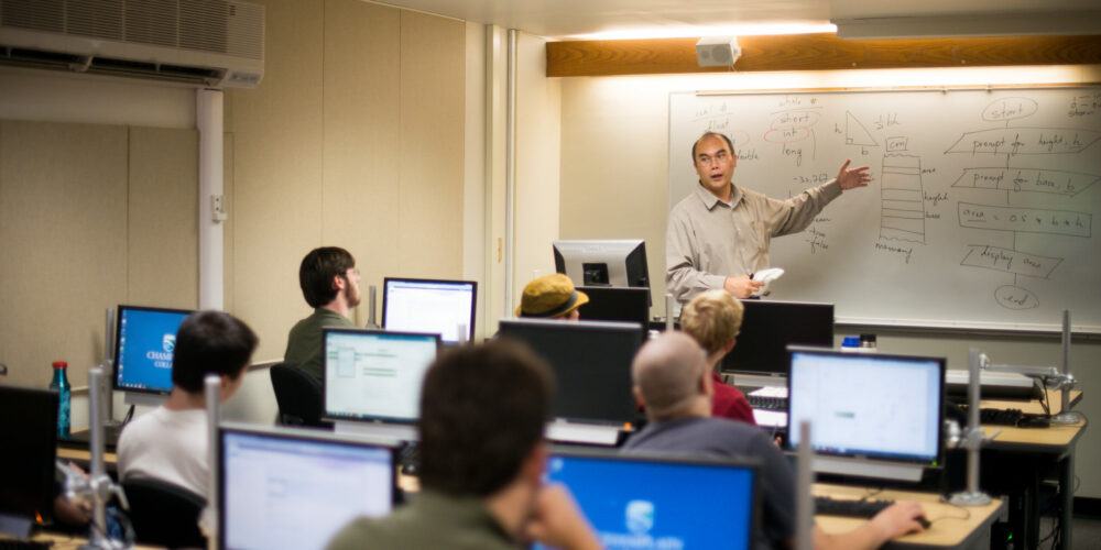 A male professor lectures at a whiteboard in front of a computer lab filled with students