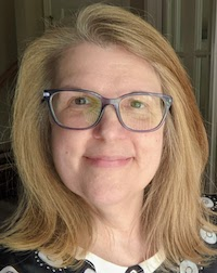 A White woman with blond shoulder-length hair and large dark brown glasses