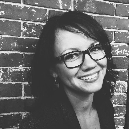 Black-and-white photo of a smiling woman with fair skin and dark hair, wearing glasses, in front of a brick wall
