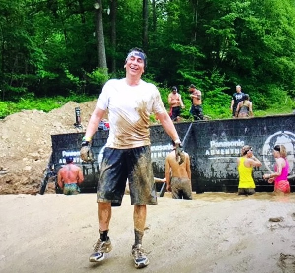 A man with dark hair wearing very muddy athletic clothes smiles in front of a muddy pond full of other racers and a black wall