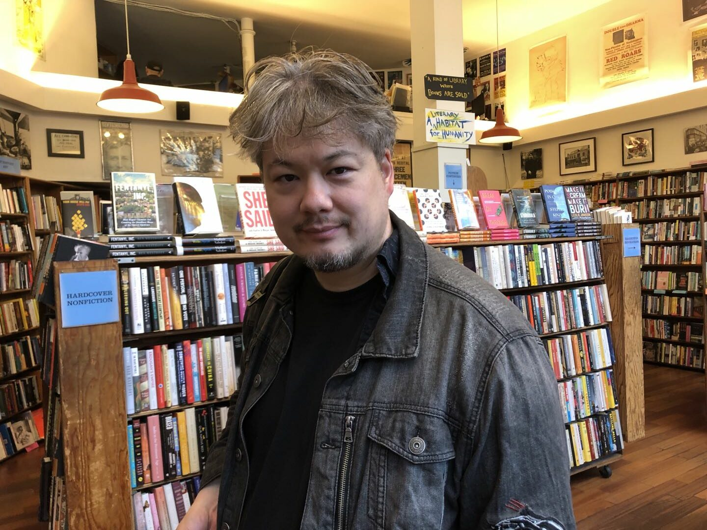 A man with dark graying hair and a small goatee beard standing in front of a full bookshelf in a bookstore