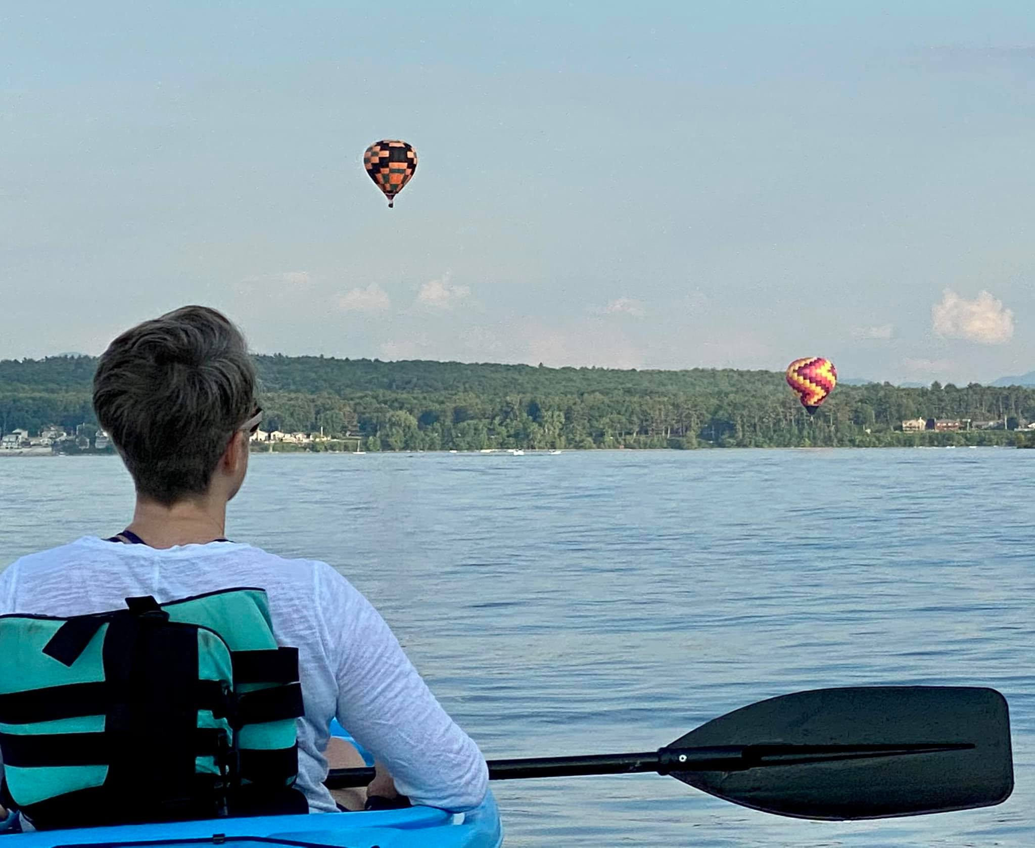 A woman with short gray hair sits in a kayak on a lake with her back to the camera, watching two hot-air balloons fly over the lake.