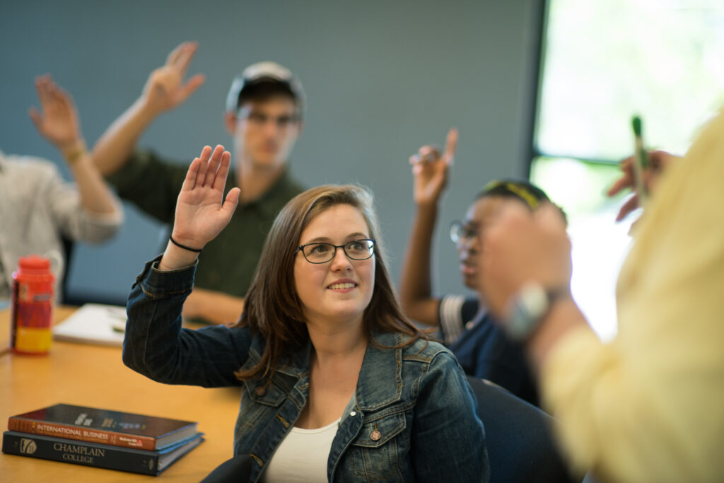 Students with hands raised in a classroom